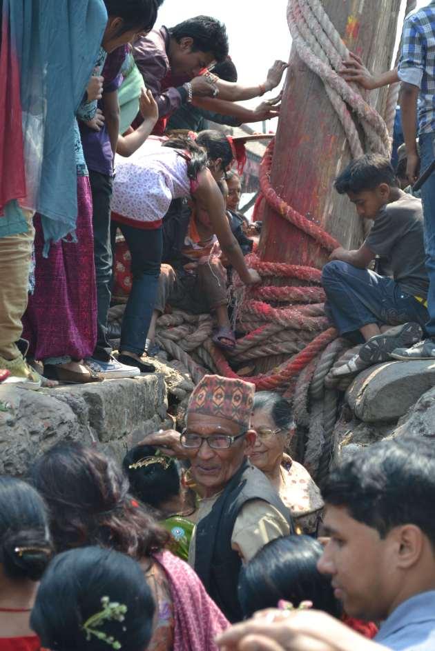 The throng aroun the base of the pillar, doing puja.