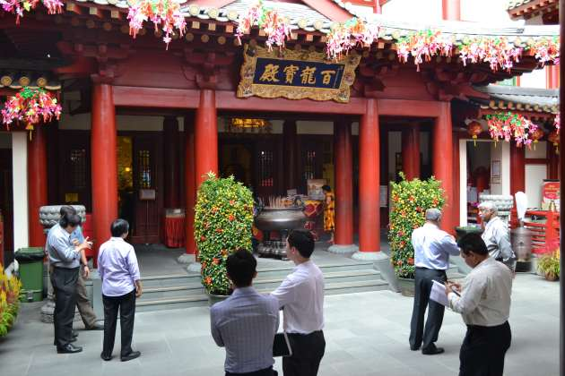 Businessmen chatting in the forecourt of the oldest Buddhist temple in Singapore